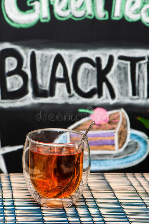 Cup with black tea on the background of graffiti with inscriptions and drawings. On a blackboard stock image