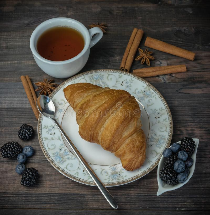 A cup of black tea with a fresh golden croissant and berries. on a wooden background. fresh bakery. royalty free stock image