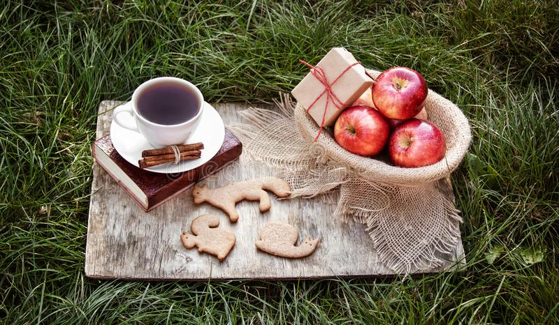 A cup of black tea, ginger cookie and a basket with red apples. Autumn harvest. stock image