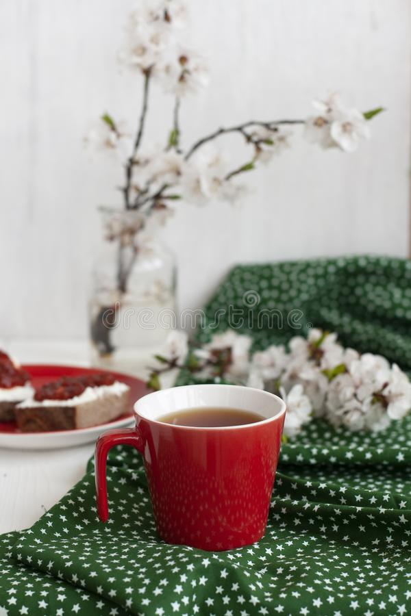 A cup of black tea on a green napkin, homemade rye bread with soft cream cheese and smoky dried tomatoes, a glass vase of apricot stock image