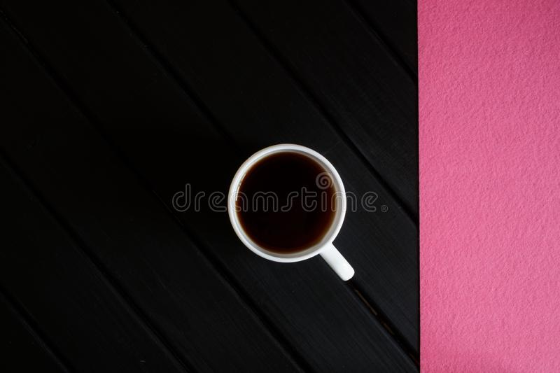 A cup of black tea and a pink napkin on a dark wooden table. View from above. Minimalism royalty free stock photos