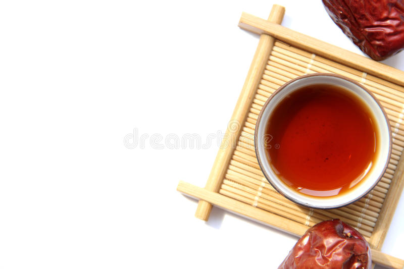 A cup of black tea with red dates. A cup of black tea on bamboo cup mat with red dates royalty free stock photo