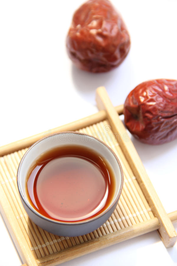 A cup of black tea with red dates. A cup of black tea on bamboo cup mat with red dates royalty free stock photography