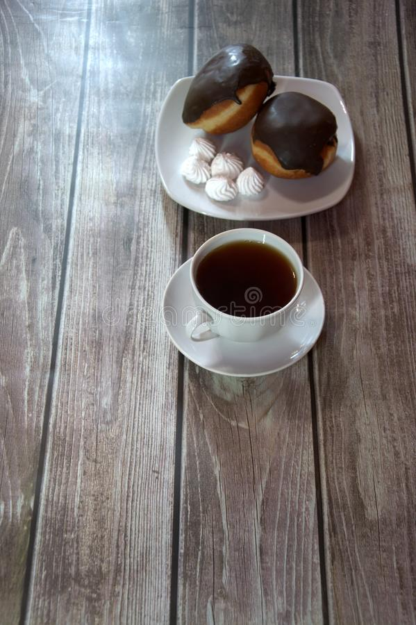 A cup of black tea on a saucer and a plate with two donuts in chocolate icing and pieces of bizet, lie on a wooden table. Close-up. A cup of black tea on a stock photography