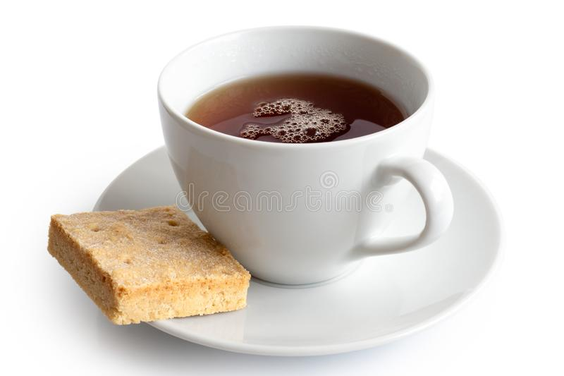 A cup of black tea with square shortbread biscuit isolated on white. White ceramic cup and saucer. stock images