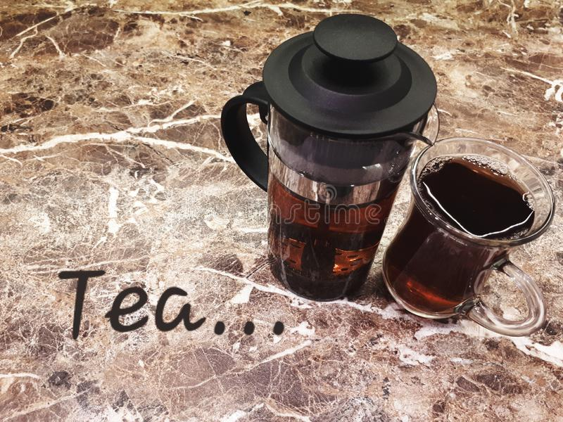 A cup of black tea and a teapot stand on a marble table. Close-up. A cup of black tea and a teapot stand on a marble table stock image