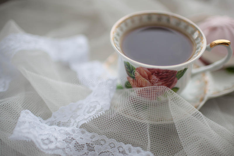 Cup of black tea on white fabric. Marshmallows next to the tea. Breakfast Bridesmaid. royalty free stock images