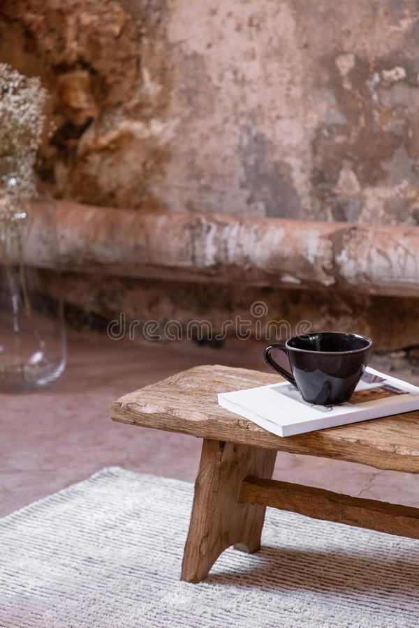 Cup and book on wooden stool on bright carpet in minimal and industrial flat interior with plant stock images