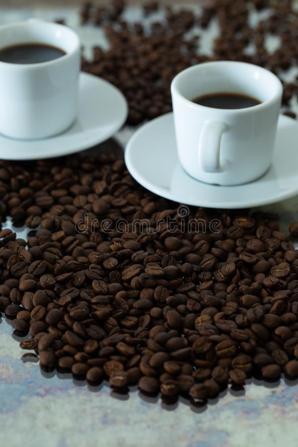 A cup of brewed coffee surrounded by whole unground beans stock images