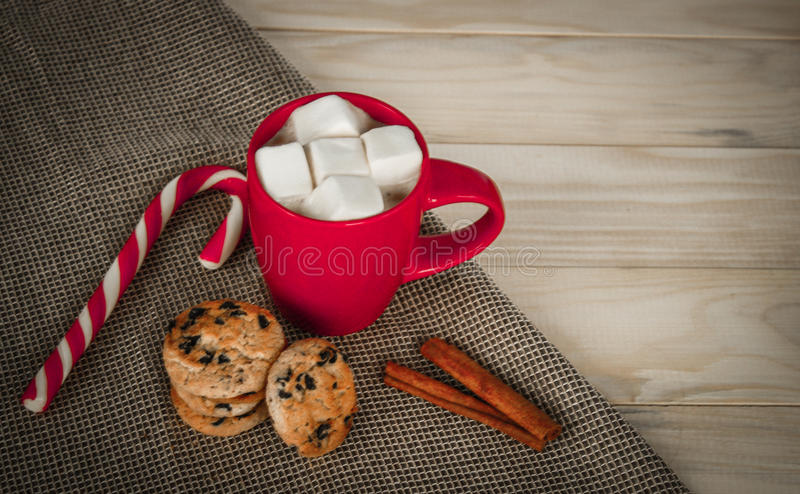 Cup of cacao on wooden background. Marshmallows and candy stick royalty free stock photography