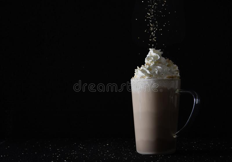 Cup of caffelatte with falling sugar. Cup of coffee with cream and sugar falling on black background and sidelight royalty free stock image