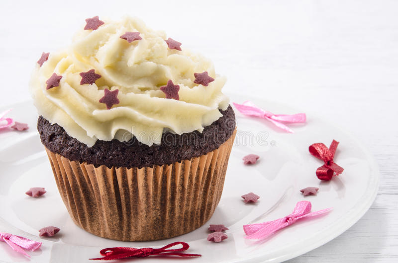 Cup cake with butter cream. And red stars stock photos