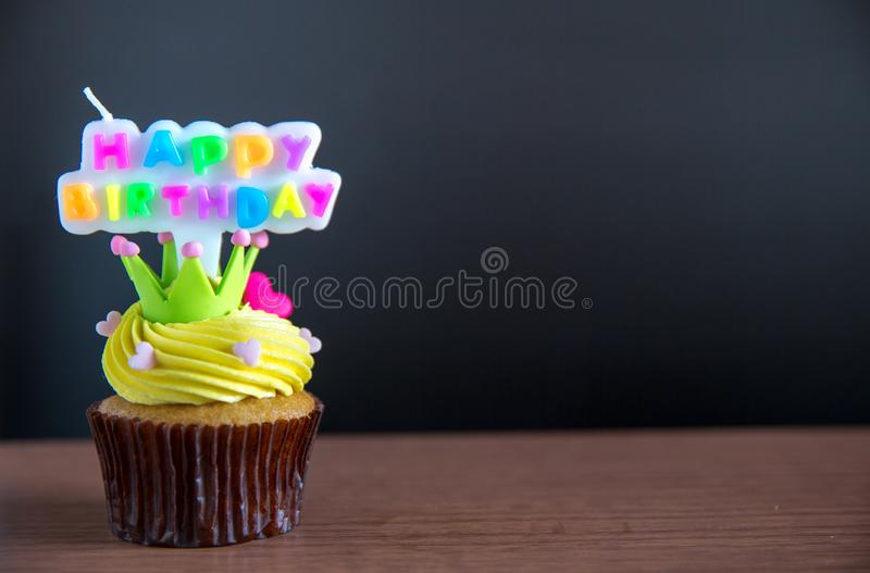 Cup cake and happy birthday text candle on cupcake ..Birthday cupcake with a happy brithday text candle. royalty free stock photos