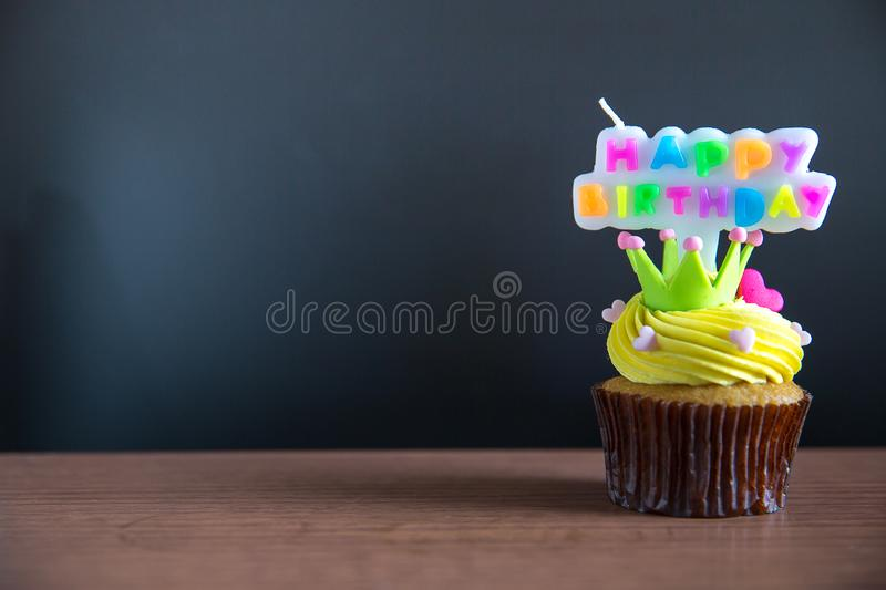 Cup cake and happy birthday text candle on cupcake ..Birthday cupcake with a happy brithday text candle. Cupcake with yellow cream and heart for love valentines stock photos
