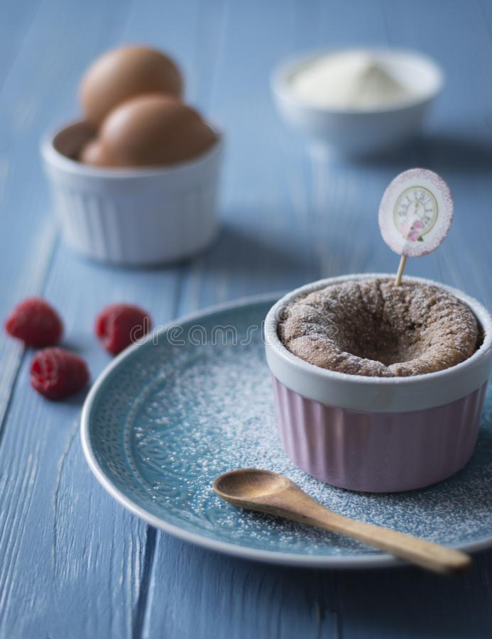 Cup cake in Retro look and harmonious blue colors. Chocolate cup cake in a pink cup on a blue plate with spoon on a Blue wood table stock photo