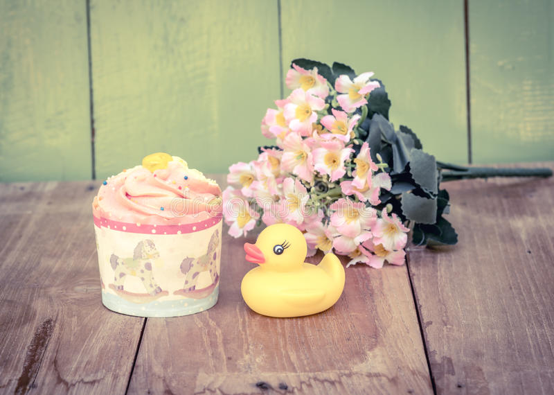 Cup cake yellow duck and plastic flower on the wood board stock photo