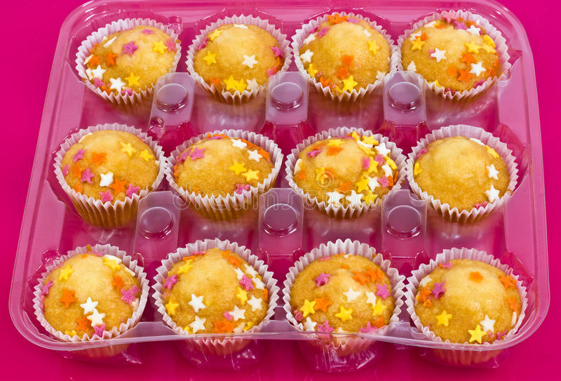 A dozen cupcakes. A closeup of a dozen shop-bought buns with star sprinkles in a plastic tray royalty free stock images