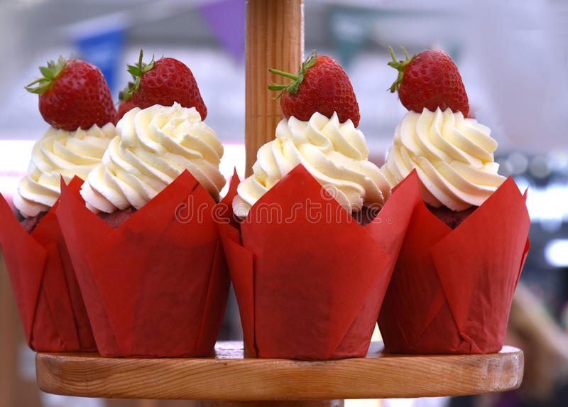 Cup cakes with whipped cream. Delicious cup cakes decorated wit cream and strawberries, a sweet temptation royalty free stock images