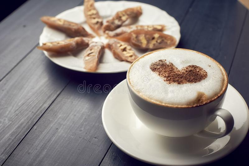 Cup of cappuccino with beautiful heart latte art on wooden table Near plate with dessert. Flat lay style. royalty free stock photography
