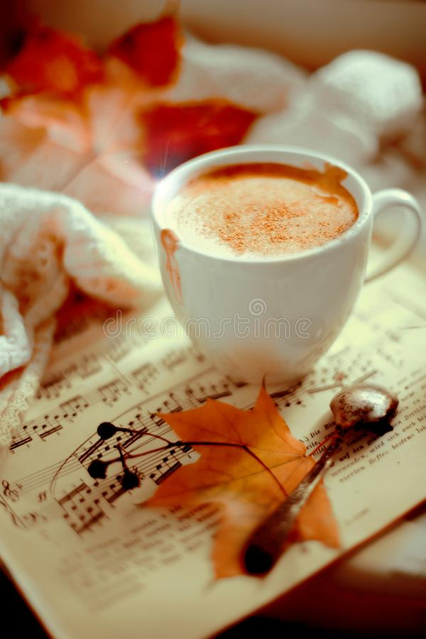Cup of cappuccino with cinnamon. Cup of cappuccino on the sheet music, autumn leaves, white knitted sweater on the windowsill in sunlight. Vertical view, copy royalty free stock photo