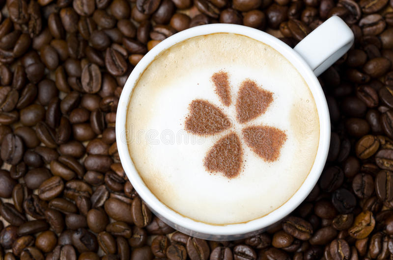 cup of cappuccino with cinnamon pattern on a background of coffee beans, horizontal stock photo
