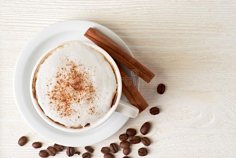 Cup of cappuccino with coffee beans and cinnamon sticks on white royalty free stock photos