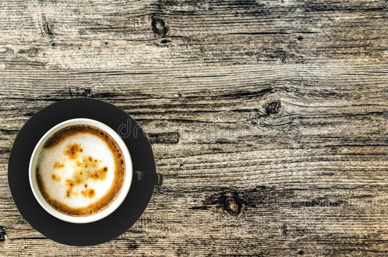A Cup of Cappuccino Coffee on the brown. royalty free stock photography