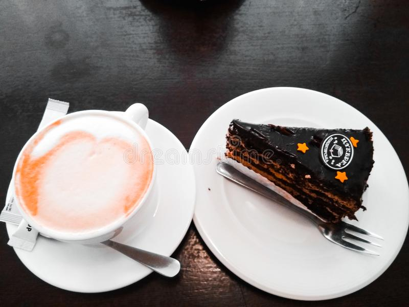 A cup of cappuccino coffee with slice of chocolate cake royalty free stock image
