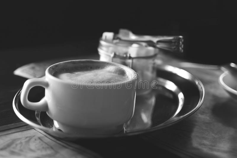 A cup of cappuccino coffee and sugar in a glass vase on a table in a cafe. Black and white photography royalty free stock photo