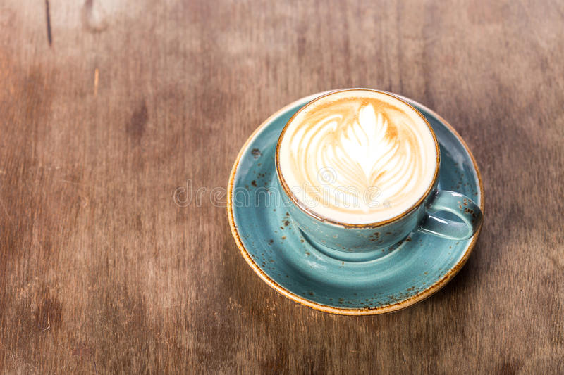 Cup of cappuccino coffee. On wooden background royalty free stock image