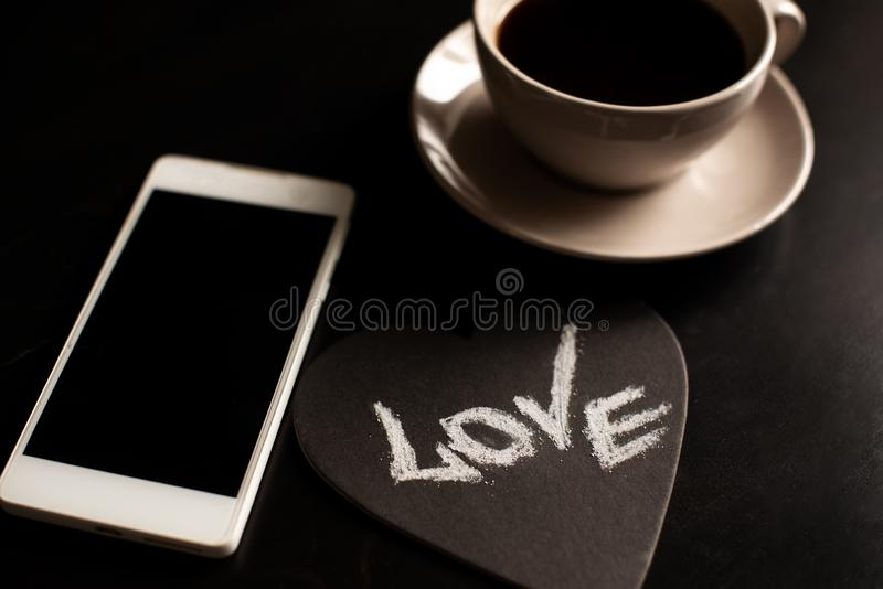 Cup of cappuccino coffee with the word love on milk froth.  royalty free stock photos