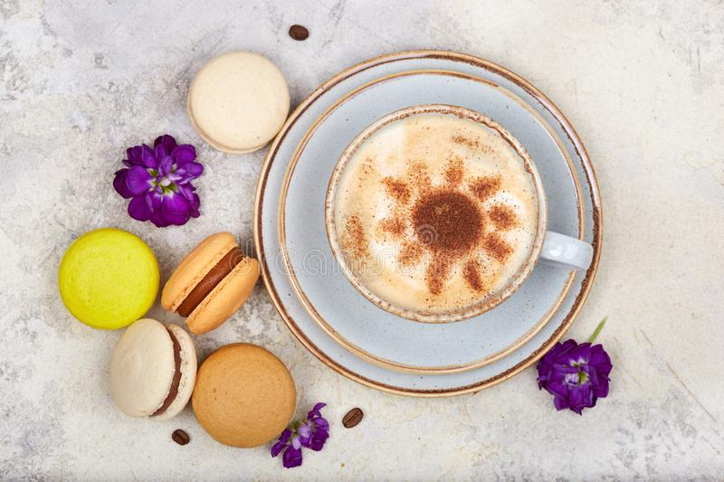Cup of cappuccino coffee and colorful French dessert macarons stock photo