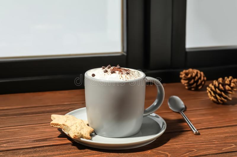Cup of cappuccino with cookies on windowsill. Winter drink. Cup of cappuccino with cookies on windowsill indoors. Winter drink royalty free stock photography