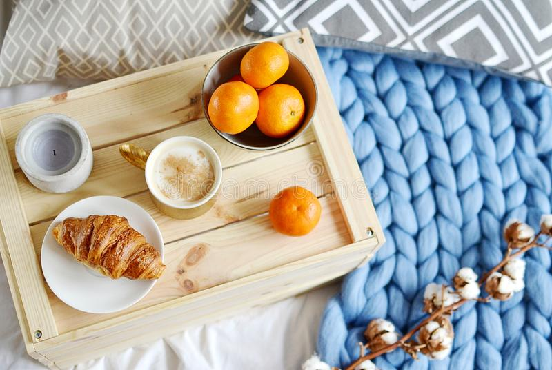 Cup with cappuccino, croissant, blue pastel giant plaid, bedroom, morning concept. Cotton flower, bowl with mandarin, candle, gray cushion stock photo