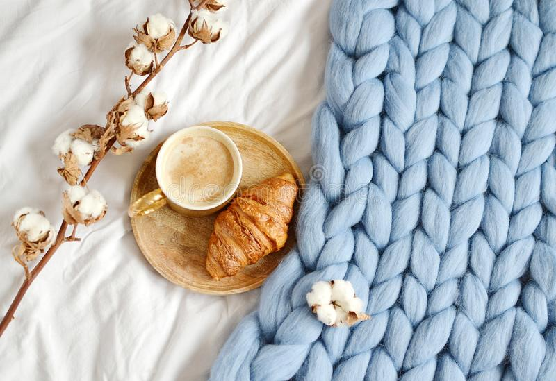 Cup with cappuccino, croissant, blue pastel giant plaid. Bedroom, morning concept, cotton flower top view royalty free stock photo
