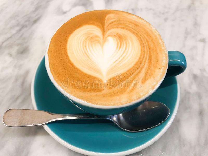 A cup of cappuccino. With latte art on top in green cup royalty free stock photo