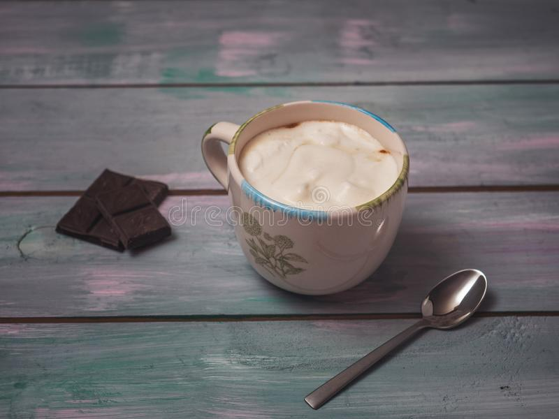 A cup of cappuccino and a few chocolate bars are on the board table. A cup of cappuccino and a few bars of chocolate lie on a plank of blue tone stock photo