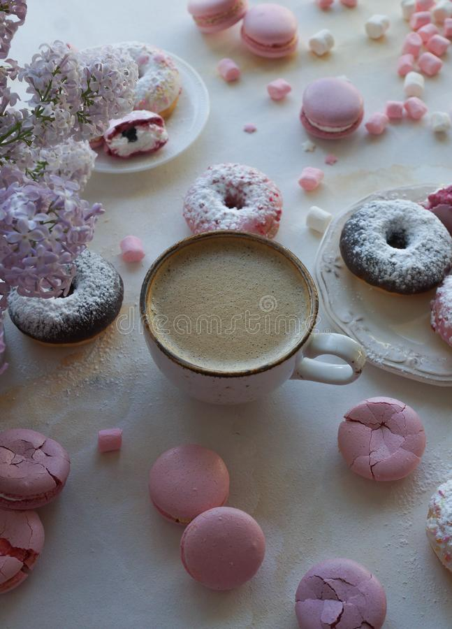 Cup of cappuccino, fresh colorful donuts, strawberry macarons and bouquet of lilac on white marble table royalty free stock images