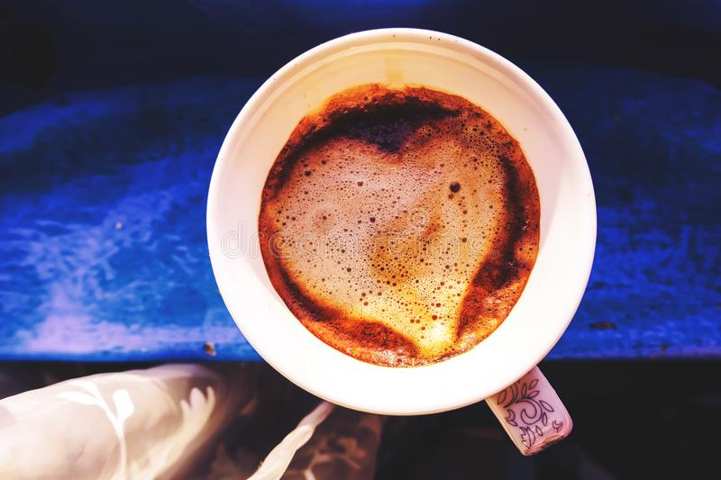 Cup of cappuccino with heart of cocoa on wooden table stock images