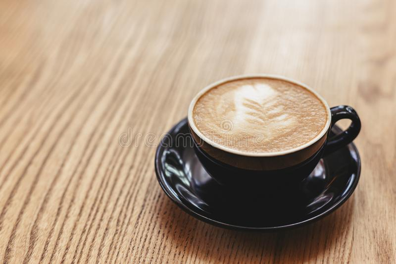 Cup of cappuccino with latte art on wooden background. Black ceramic cup. Cup of cappuccino with latte art on wooden background. Black ceramic cup, place for stock photos