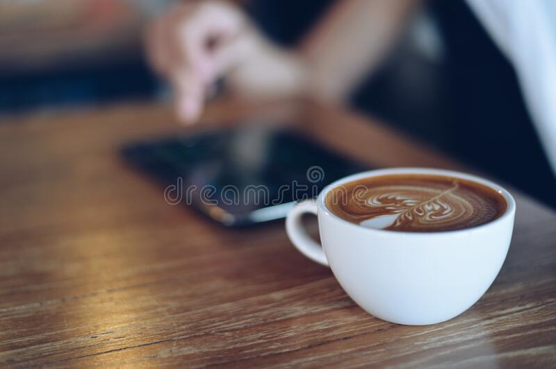 Cup of cappuccino and mobile phone royalty free stock photography
