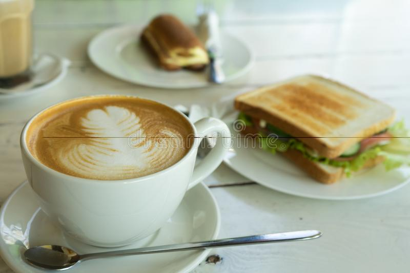 A cup of cappuccino and sandwich ham cheese on the plate stock photography