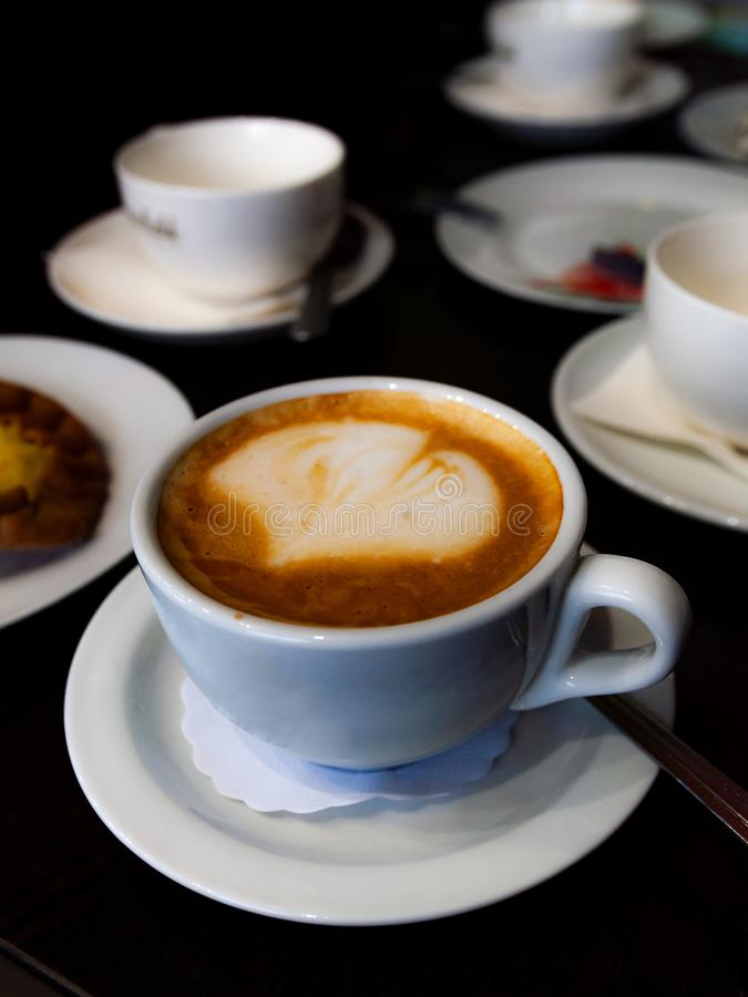 Cup of cappuccino on the table. Among other utensils stock image