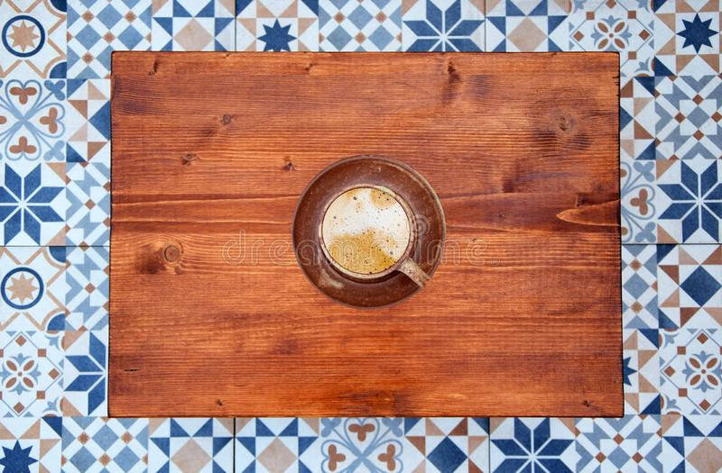 Cup of cappuccino on wooden background top view. Cup of coffee on wooden table and mosaic tiles floor background. Fresh cappucino on coffee table top view royalty free stock photo