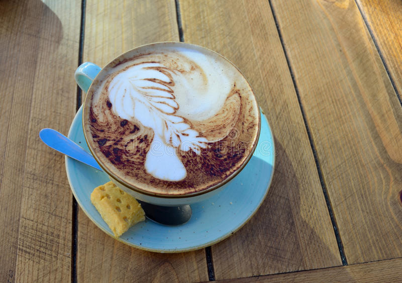 Cup of Cappuccino on wooden table stock photography