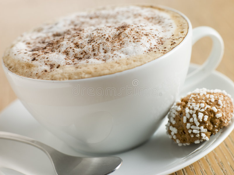 Cup of Cappucino. Close up of Cup of Cappucino with an Amaretti Biscuit stock photography