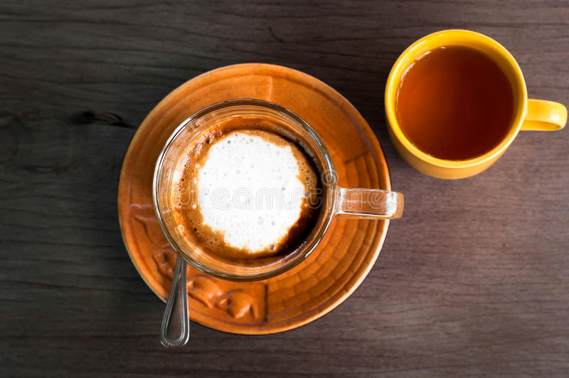 A cup of caramel cappuccino coffee in a transparent cup on wooden background with hot tea in yellow cup royalty free stock image