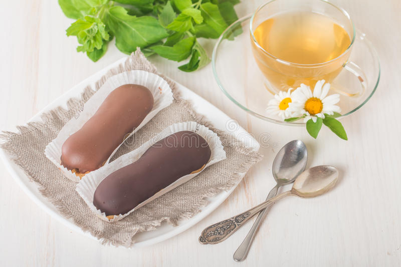 Cup of chamomile tea with chocolate eclairs. On white background royalty free stock photography