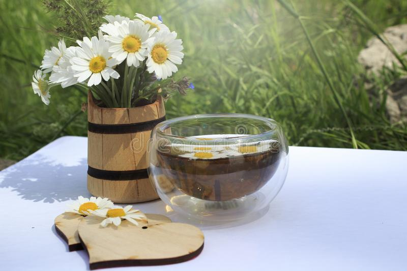 Cup of chamomile tea on a wite background. With two wooden hearts and a bouquet of chamomiles stock photo