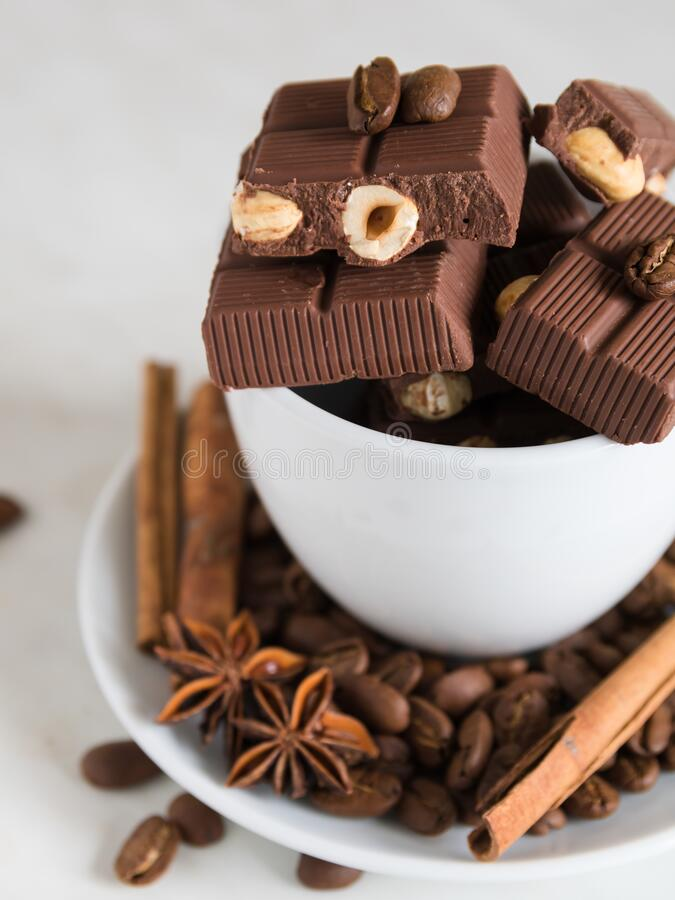 still life, installation, a cup with chocolate, coffee beans, anise and cinnamon sticks on a marble table stock photography